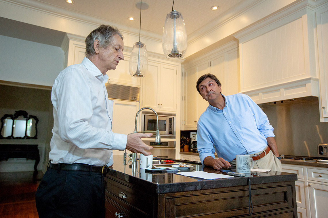 University Professor Emeritus Geoffrey Hinton and U of T President Emeritus Dr. David Naylor discuss the transformative impact of AI on health care in the kitchen of Naylor's Toronto home (photo by Lisa Lightbourn)