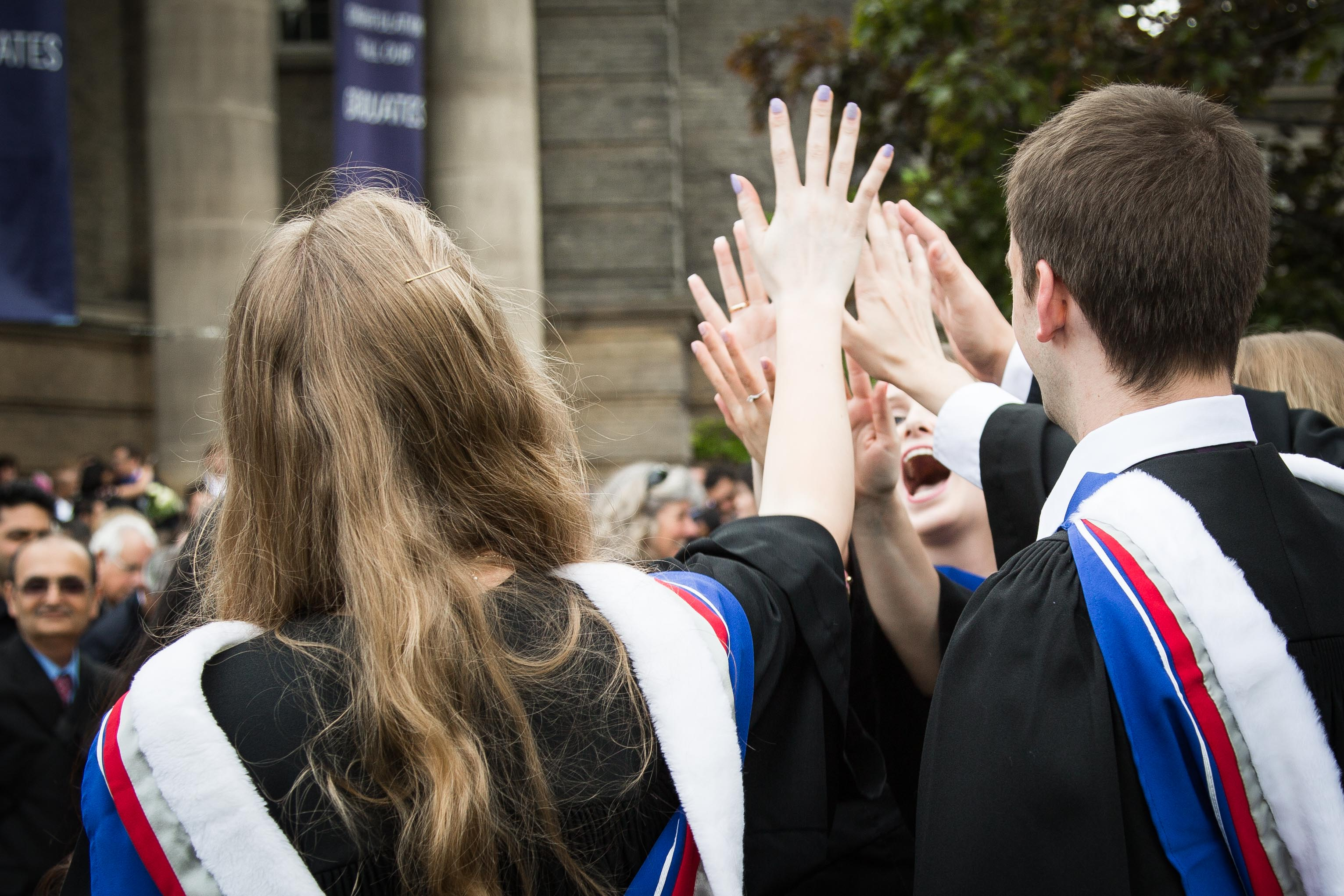 Students high five after graduating from the MD Program