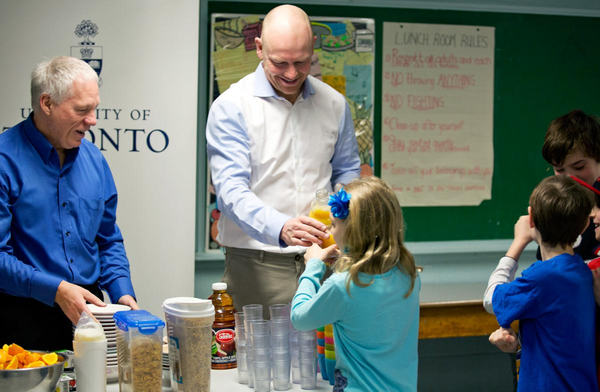 Dr. Stephen Lye (Left), Professor in the Departments of Obstetrics and Gynaecology and Physiology, and Mats Sundin serve a nutritious breakfast to elementary school students.