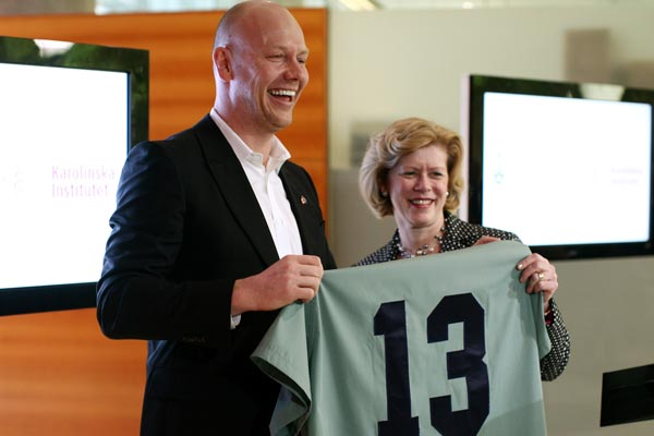 Former Toronto Maple Leafs captain Mats Sundin beams as he and Dean Cathy Whiteside display the U of T Faculty of Medicine's gift of medical scrubs bearing his iconic No. 13. (Photo by Dave Chan)
