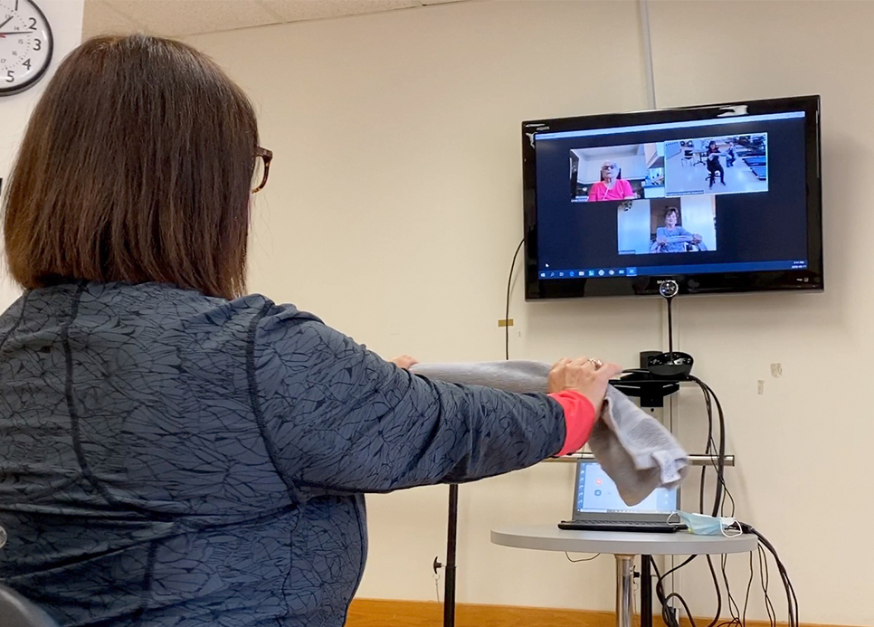 A woman leads a virtual rehabilitation class.